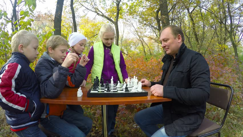 Group Of Happy Children Enthusiastically Playing Chess With A Man Family Life
