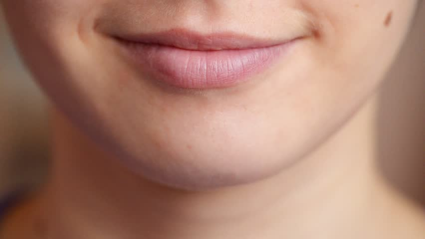 Close up of young woman licking her lips
