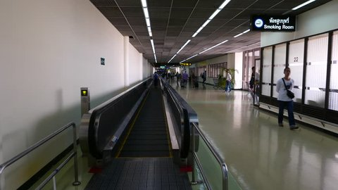 BANGKOK - MARCH 30, 2015: POV slide on travellator, old international airport, alert announce sound 'watch your step'. Don Mueang airport, located at Bangkok city. Rather empty departure terminal area