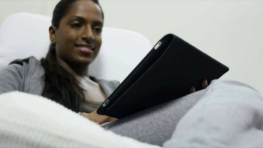 close up of mid adult Indian woman relaxing on sofa and using touch pad computer. selective focus on hand