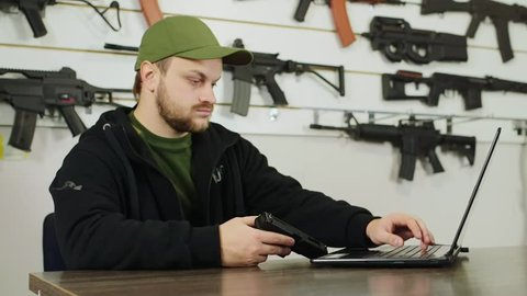 A man working at a laptop in gun shop, holding a gun in his hand