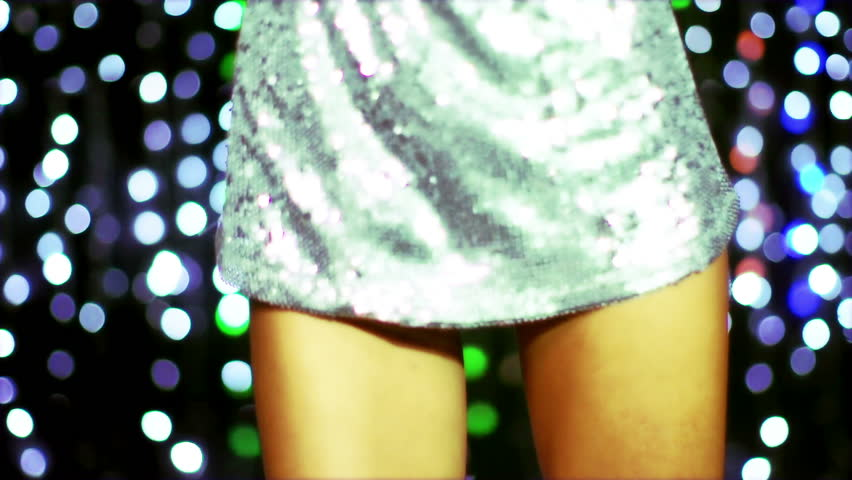 a sexy woman dances in a sparkly disco dress, shot in high quality slow motion