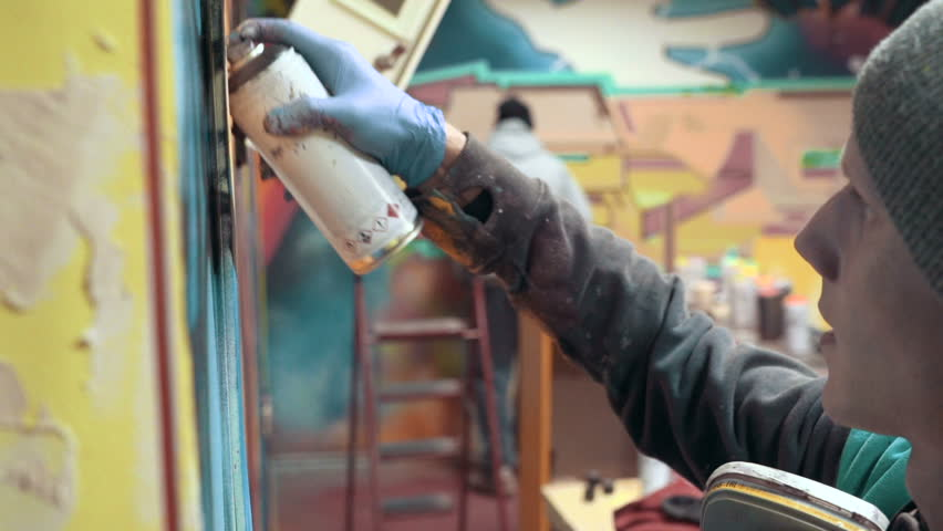 Graffiti artist painting on the wall, interior, slow motion