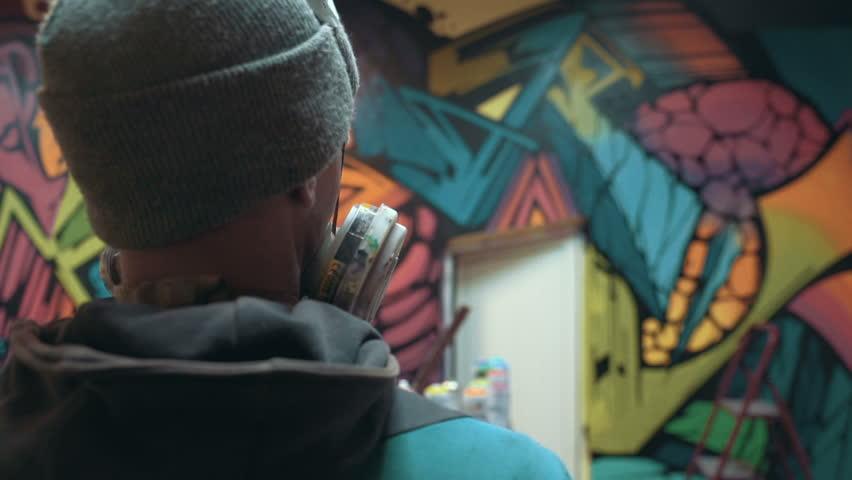 Graffiti artist watching at his work, interior