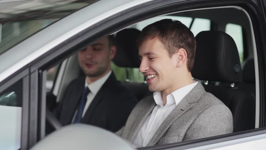 Young man and car seller takling in the car   Shutterstock HD Video #12929648
