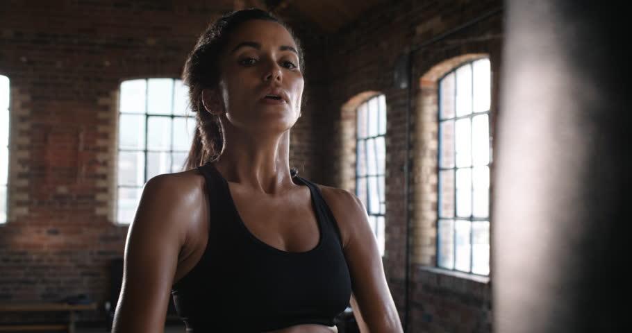 Beautiful Kickboxing woman training punching bag in fitness studio fierce strength fit body kickboxer