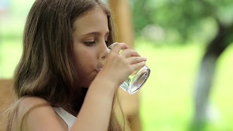 Beautiful girl drinks clean water from a glass