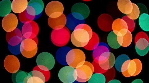 Defocused colorful lights in darknes change sizes and form by change aperture