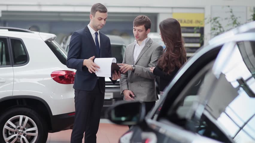 Car salesman shows a young couple information about their new car