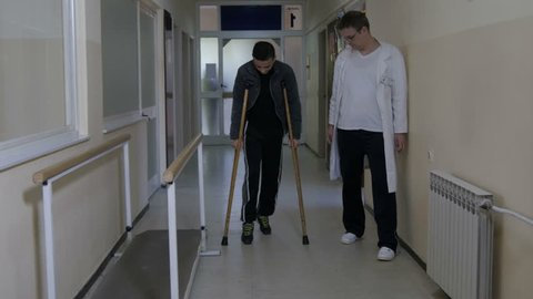 The boy learning to walks with crutches after removing bandage from broken ankle with male physiotherapist support.Treatment and rehabilitation of injured young adult in hospital center,no grading.