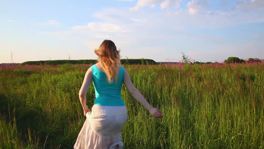 Young woman running in field.