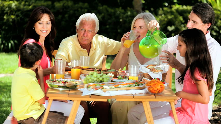 three generations of caucasian family sitting outdoors sharing a healthy lunch together hd stock video