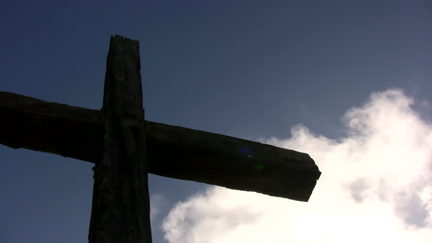 A large cross with white clouds floating behind it.