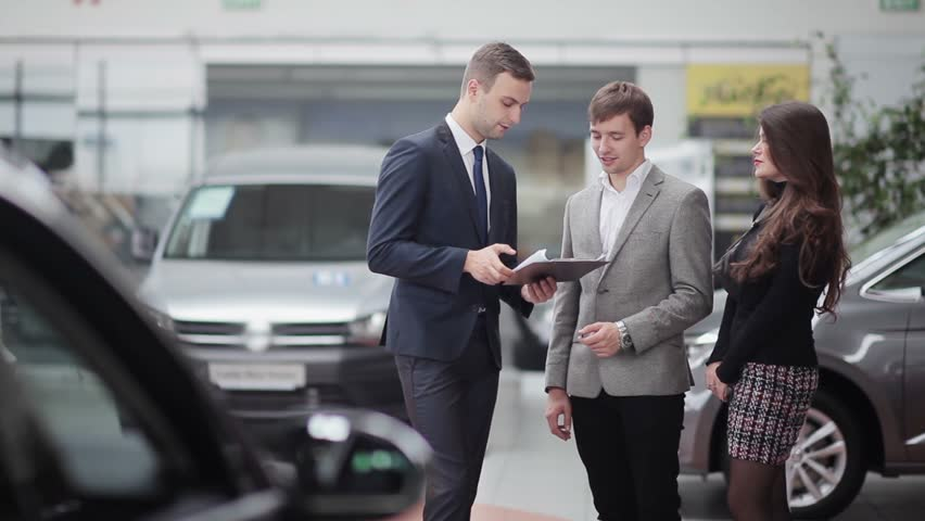 Salesman transmitting keys to young couple in car dealership | Shutterstock HD Video #13048955