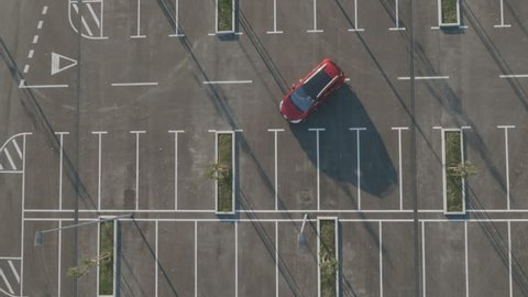 Aerial, departing car in empty parking lot