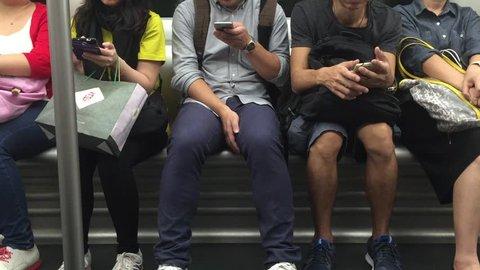 HONG KONG, CHINA - NOVEMBER 23, 2015: People using smart phones inside MTR subway wagon while riding. Concept of lack of communication in modern society.
