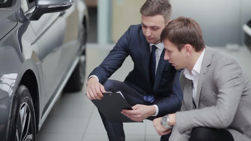 Seller shows the customer various car options in dealership