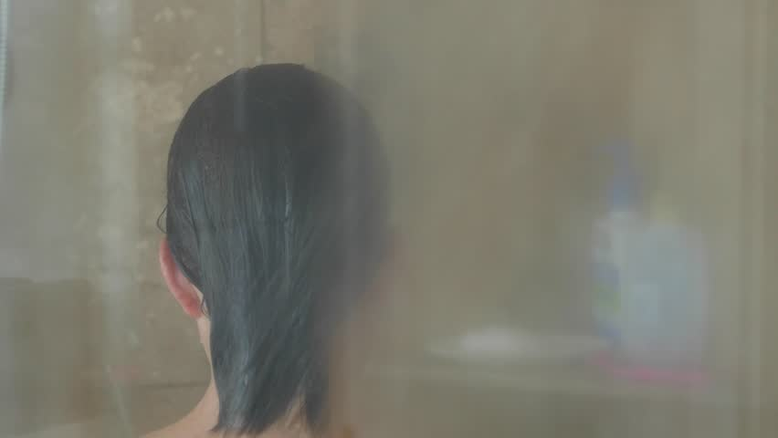 A dolly shot of a beautiful woman in a glass and tile shower washing her long hair