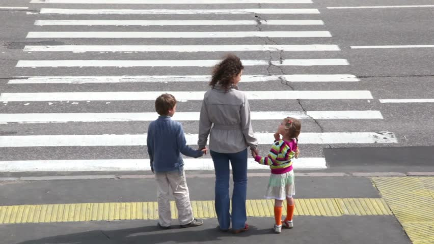 Mother and her two children, boy and girl, cross road at pedestrian crossing after car drove and other stopped to let them pass, then cars ride