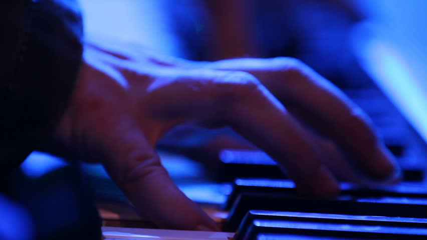 Close up of hands playing a keyboard in a creepy lighting setup.  Looks like lightning is striking while he plays.