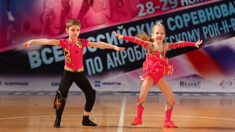 """MOSCOW, RUSSIA - NOVEMBER 29, 2015: Little dancers. Children pair incendiary dance sports acrobatic rock-n-roll. National competition in acrobatic rock-n-roll at the Palace of sports """"Dynamo""""."""