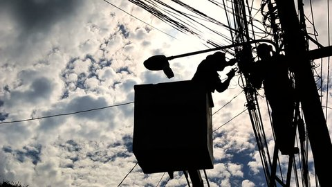 Silhouette of an electrician to repair street lighting