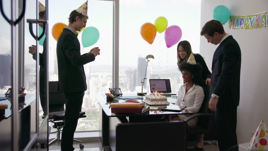Business woman celebrating 27 years and doing a party with colleagues in her office. A friend with mobile phone takes pictures of her blowing out candles on birthday cake. Wide shot