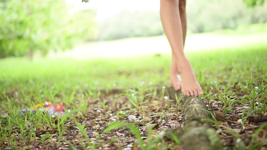 Lonely Girl feet without shoes walking on the big tree root in the park | Shutterstock HD Video #13135625