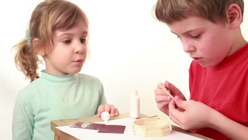 Girl tell something to boy which apply glue on match and attach it to wall of match house, she just touch the cap of glue bottle but it made boy angry