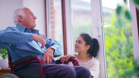 4K Caring young home support worker spending time with elderly gentleman in his home. Shot on RED Epic