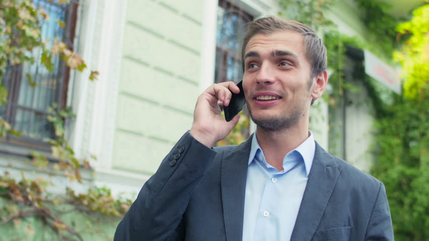The businessman costs in the downtown and communicates with someone by phone. The man looks very happy.  | Shutterstock HD Video #13177181
