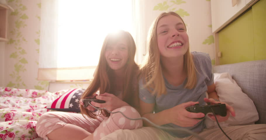 Teen girl on a bed pushing her laughing friend in a joking way while playing computer games at a daytime pyjama party