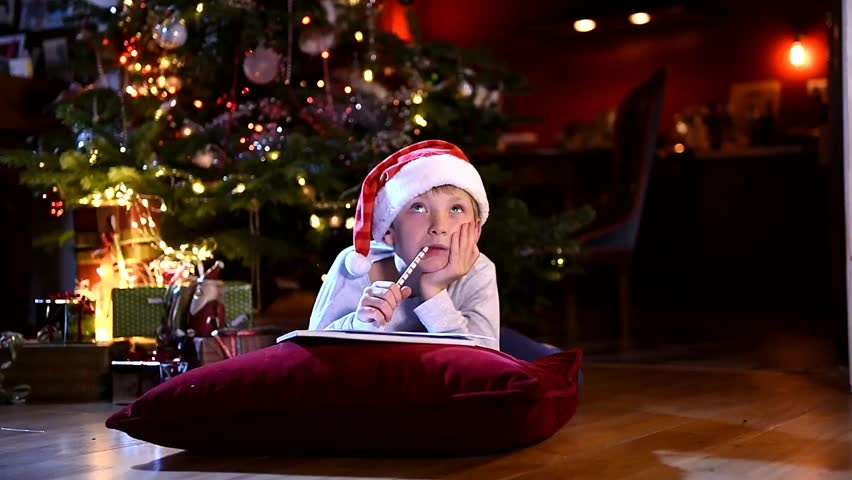 Christmas time, a little boy with a santa hat lying on a cushion is thinking to write his wish list to santa claus, at background the christmas tree illuminated with gifts on the floor