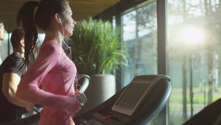 Attractive caucasian girl running on the treadmill in the sport gym with phone and earphones. Shot on RED Cinema Camera in 4K (UHD). | Shutterstock HD Video #13216154