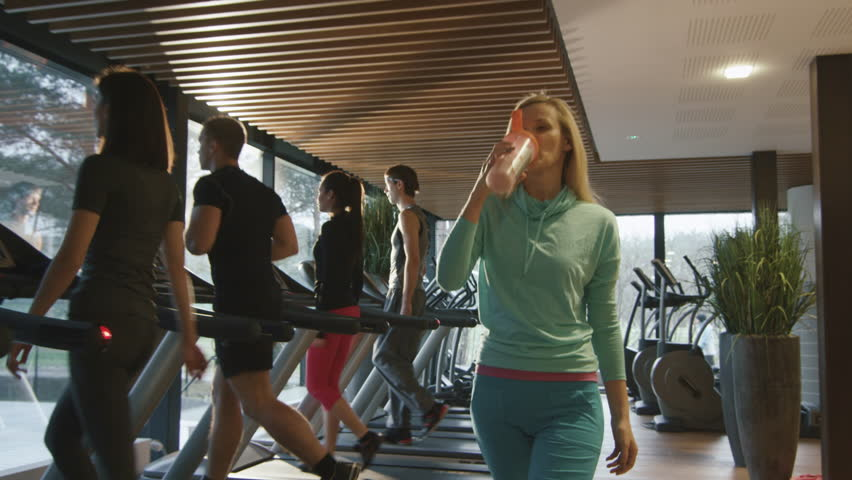 Attractive blond caucasian girl is drinking a protein shake drink while walking next to a treadmill in the sport gym. Shot on RED Cinema Camera in 4K (UHD).