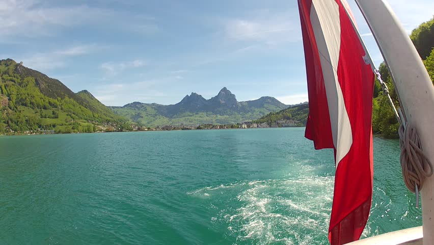 Lake in Switzerland with flag and mountains in background.