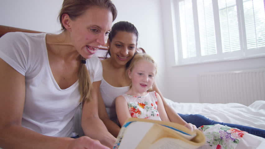 4K Happy family life - gay female couple relaxing at home & reading with  daughter. Shot on RED Epic.