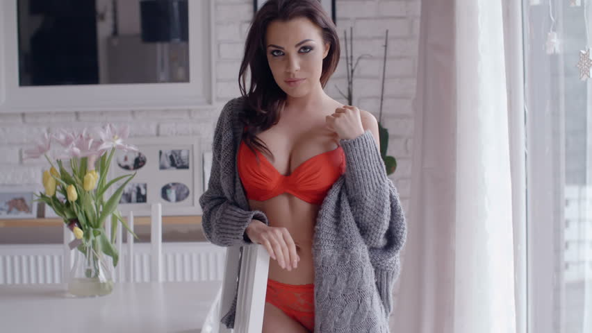 c5590a8899c Sexy Young Woman Posing in Orange Underwear with Gray Cardigan Inside the  House While Looking at the Camera Sensually.