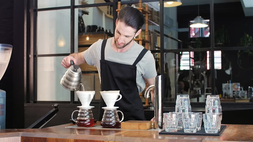 Hipster barista with beard brews two different coffees to compare the tasting profile of different beans