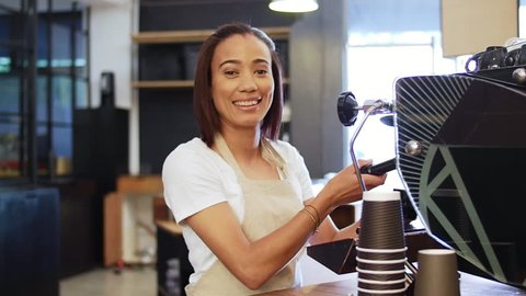 Smiling portrait of happy friendly passionate female woman barista in modern trendy cafe working the coffee machine