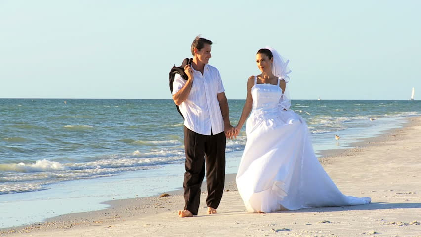 Bride & bridegroom walking barefoot on the beach after their wedding ceremony filmed at 60FPS
