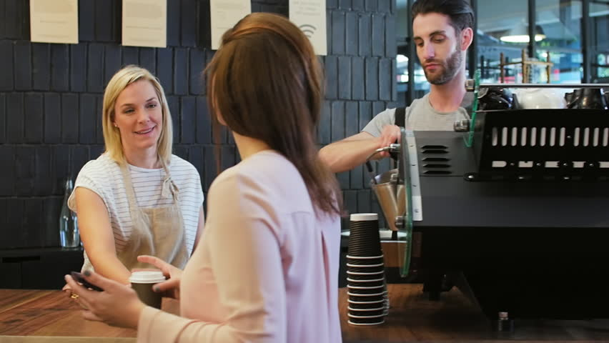 Barista at coffee machine, friendly waitress serves coffee and interacts with customer for orders in modern trendy cafe coffee shop