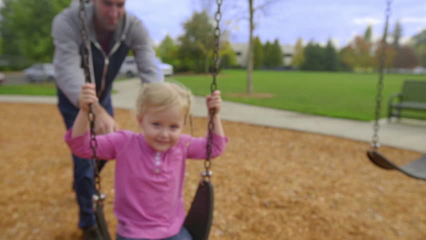 Father pushes his daughter on a swing as she smiles for the camera