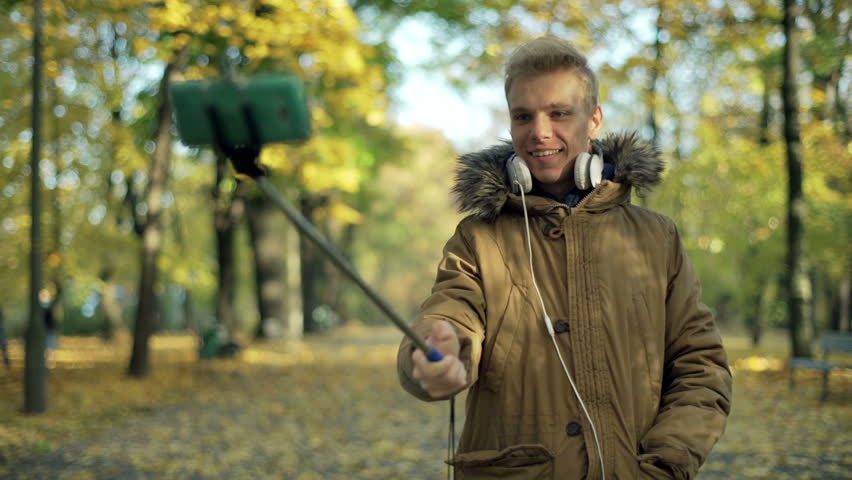 Man using selfiestick and recording on smartphone in the park  #13315325