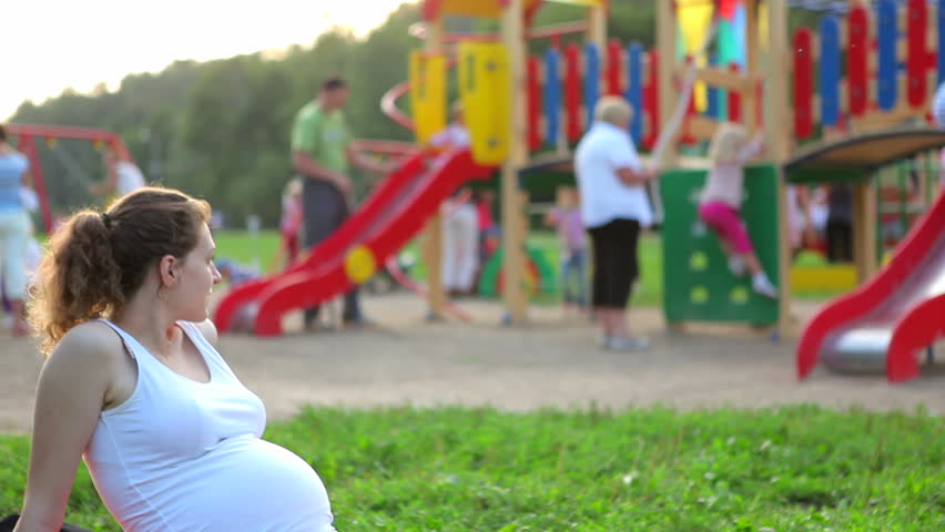 Pregnant woman watching the children on the playground