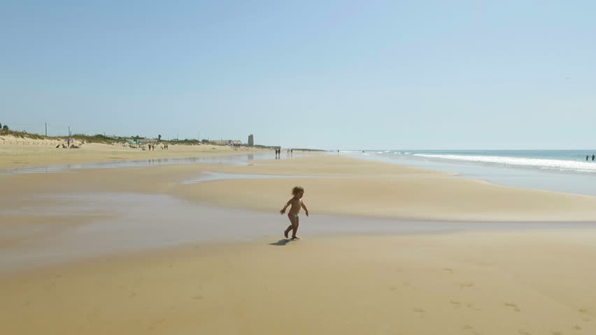 Two years old blonde baby with green swimwear walking at golden sand beach in Vejer and Palmar coast in Cadiz Andalusia Spain | Shutterstock HD Video #13327415
