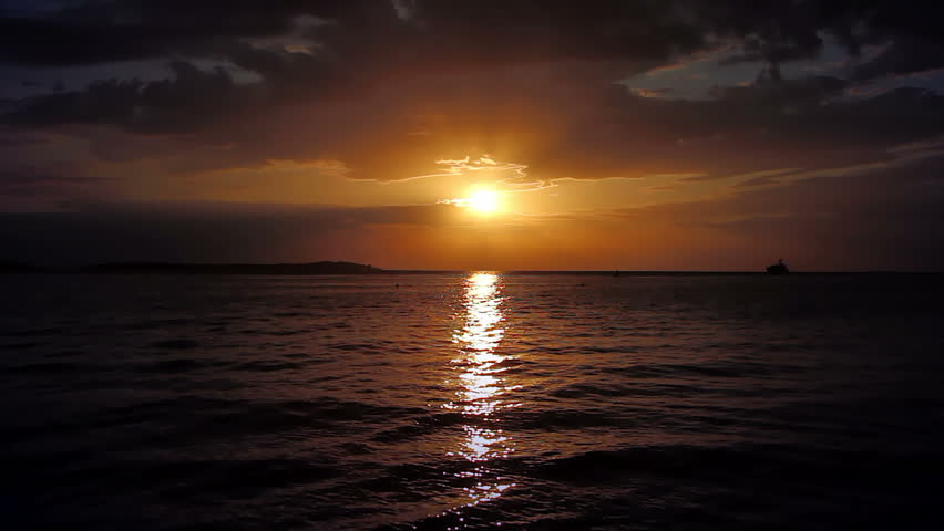 Seascape, calm water surface and cloudy sky on sunset