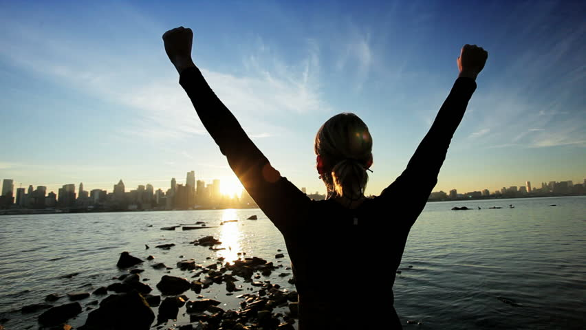 Female in silhouette saluting the challenge of a new day with a city skyline backdrop at sunrise