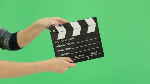 hand girl with clapperboard on the green screen. blue manicure nails