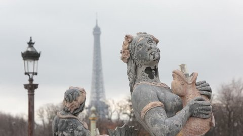 Architectural detail of character on the 'Fontaines de la Concorde' at 'Place de la Concorde' in the center of Paris with focus pull to Eiffel tower